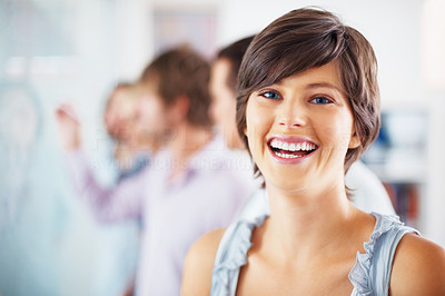 Buy stock photo Focus on cheerful young woman with her team discussing in background