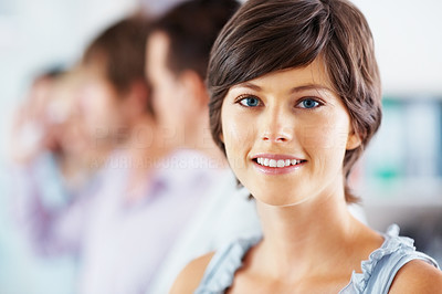 Buy stock photo Closeup of smiling young woman with her team in background