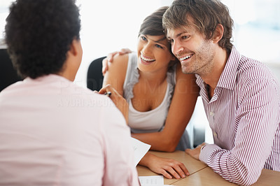 Buy stock photo Cheerful couple discussing financial matter with advisor
