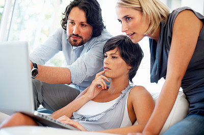 Buy stock photo Handsome business man showing beautiful and successful colleagues something on laptop