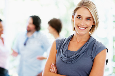 Buy stock photo Focus on pretty woman with colleagues talking in background
