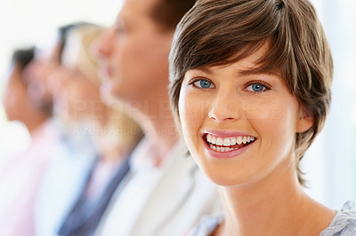 Buy stock photo Focus on happy woman with team in row in distance