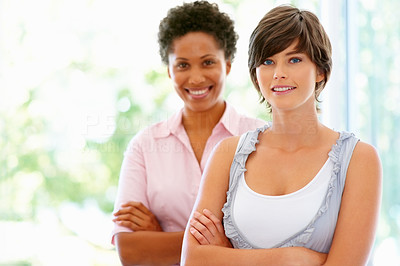 Buy stock photo Two women standing with arms folded