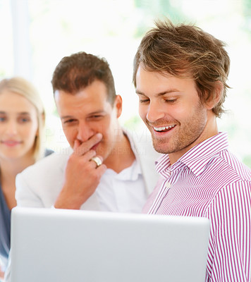 Buy stock photo Handsome man showing team something on laptop and smiling