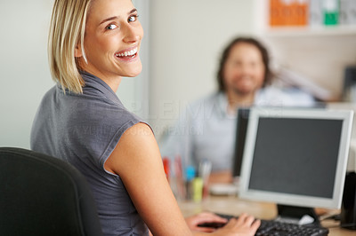 Buy stock photo Attractive business woman working on computer and smiling at you