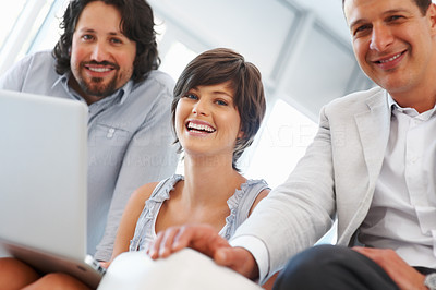 Buy stock photo Pretty young business woman with colleagues using laptop and smiling