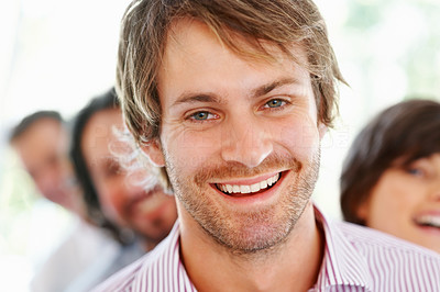 Buy stock photo Closeup of handsome young business man with team in background