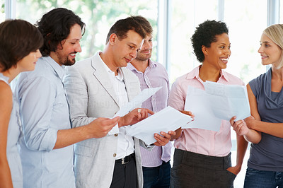 Buy stock photo Leader reviewing documents to his team