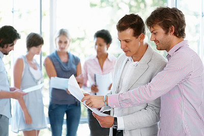 Buy stock photo Young man showing paperwork to his leader with team in blur background