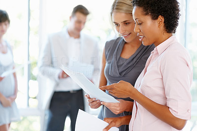 Buy stock photo Business women going through documents with team in background