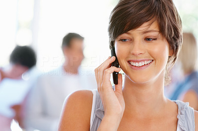 Buy stock photo Closeup of beautiful young woman speaking on cell phone with team in background