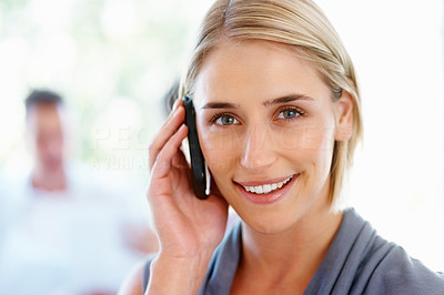 Buy stock photo Closeup of beautiful young woman talking on cell phone with team in background