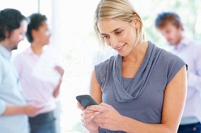 Buy stock photo Woman sending text message on cell phone with team in background