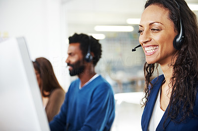 A pretty call center agent smiling and looking at her computer screen