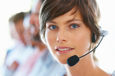 Buy stock photo Pretty young executive wearing headset with team in blur background