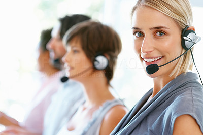 Buy stock photo Smiling young executive wearing headset with team in blur background