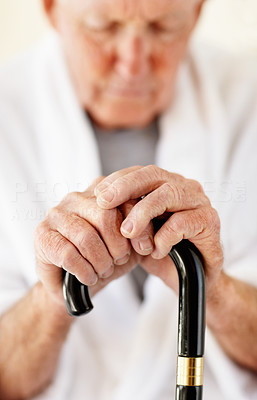 Buy stock photo Closeup of a senior man's hands resting on his walking stick