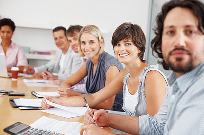 Buy stock photo Focus on young woman with her colleagues in meeting room