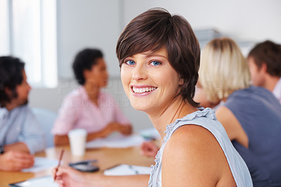 Buy stock photo Smiling woman taking notes while looking at you in meeting