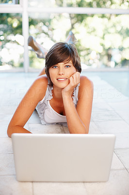 Buy stock photo Attractive young woman with laptop lying on the floor