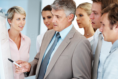 Buy stock photo Mature male business executive training his associates during a meeting at office