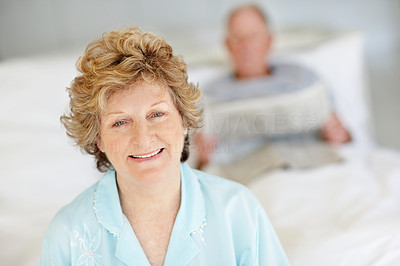Buy stock photo Portrait of a happy-looking senior woman sitting on the bed with her husband lying in the background
