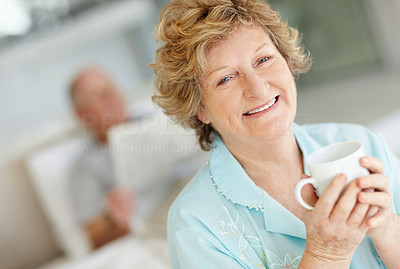 Buy stock photo Portrait of a smiling woman with her husband lying in bed behind her