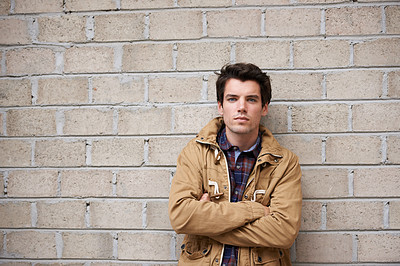 Cropped shot of a young man leaning against a brick wall with his arms crossed