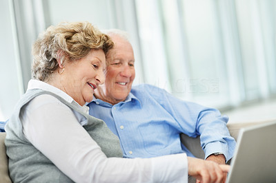 Buy stock photo A senior couple sharing a laptop while sitting on their sofa