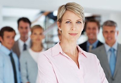 Buy stock photo Portrait of a successful businesswoman standing with her team in background