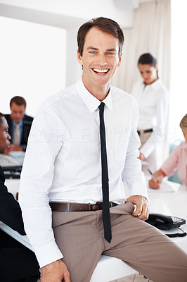 Buy stock photo Portrait of a smiling young businessman sitting on desk and his colleagues working behind at office