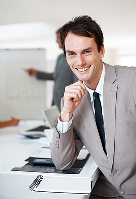 Buy stock photo Portrait of a happy young businessman sitting by the desk at office