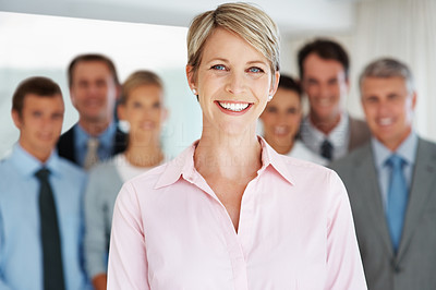 Buy stock photo Portrait of a happy young businesswoman smiling and her colleagues standing behind
