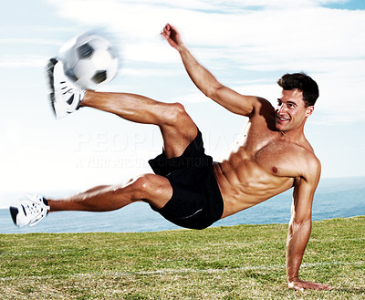 Young soccer player kicking the football in action