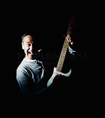 Mature man playing an acoustic guitar against black background