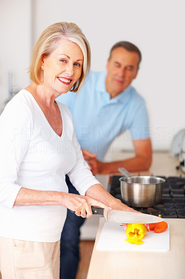 Smiling senior woman preparing food with man in background