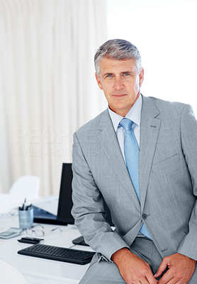 Buy stock photo Portrait of a successful mature businessman sitting on desk at office