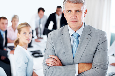 Buy stock photo Portrait of a confident businessman with his team working in background