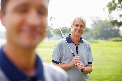 Senior man holding a golf club and smiling