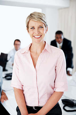Buy stock photo Portrait of a successful young businesswoman smiling with colleagues in background