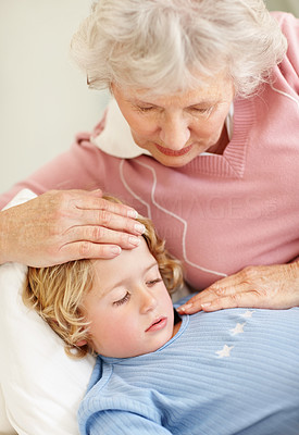 Buy stock photo Portrait of a caring grandmother feeling the forehead of a sleepy boy