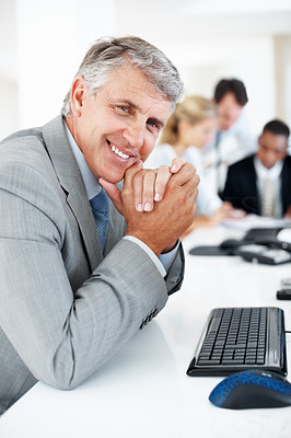 Buy stock photo Successful mature businessman sitting relaxed at his desk with his team working in background