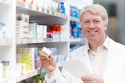 Smiling pharmacist with medicine and prescription