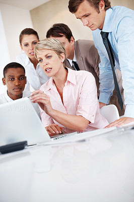 Buy stock photo Portrait of a confident businesswoman discussing work with colleagues using laptop