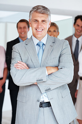 Buy stock photo Portrait of a smart senior manager standing with his team in background