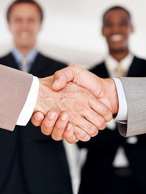 Buy stock photo Closeup of a business hand shake between two businessman with colleagues standing in background