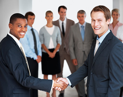 Buy stock photo Happy business people greeting each other at office with team standing in background