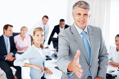 Buy stock photo Portrait of a mature businessman offering a handshake with his team working in background
