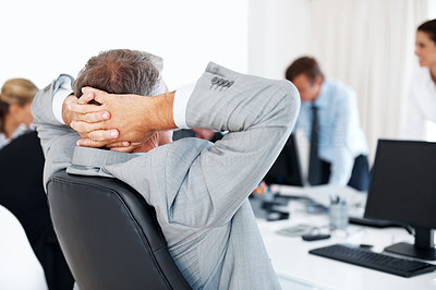 Buy stock photo Rear view of a senior manager relaxing on the chair and his team working in an office