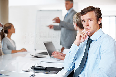 Buy stock photo Portrait of a serious business man looking at you with colleagues in background at a presentation